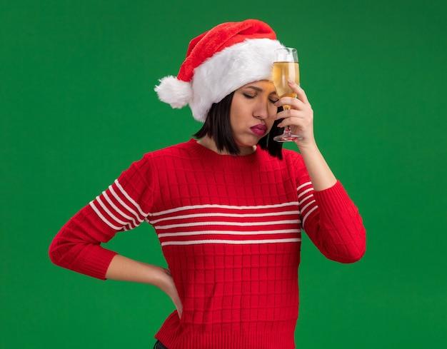 Stanco giovane ragazza che indossa santa hat tenendo un bicchiere di champagne toccando la fronte con esso sbuffando guance con gli occhi chiusi mantenendo la mano sulla vita isolato su sfondo verde