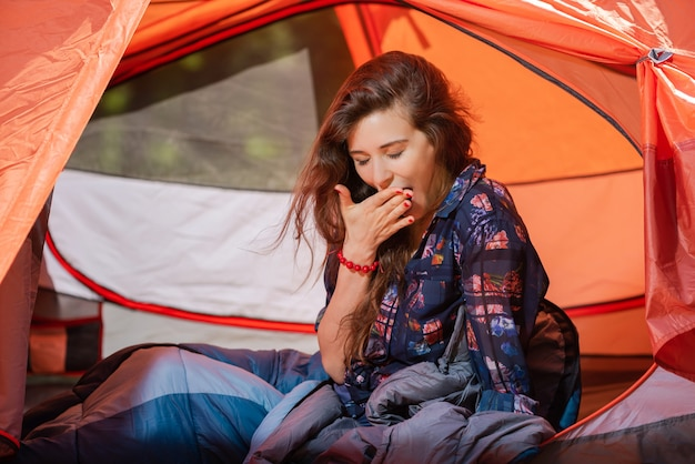 Tired young girl yawning at tent inside
