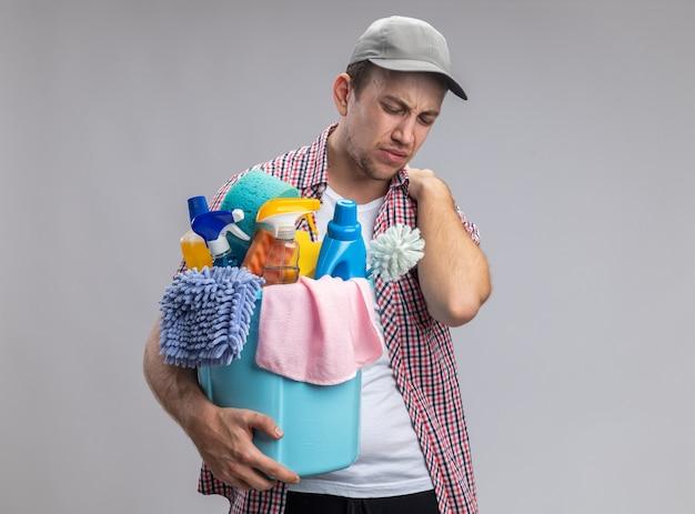 掃除道具のバケツを保持しているキャップを身に着けている疲れた若い男クリーナーは、白い背景で隔離の肩をつかんだ