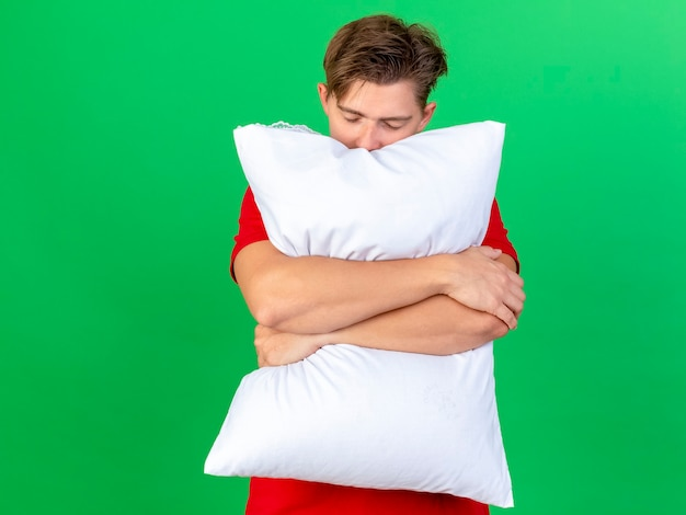 Tired young handsome blonde ill man holding pillow with closed eyes isolated on green wall