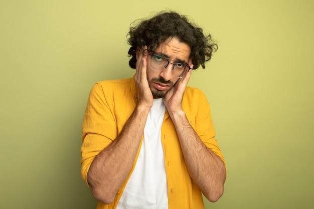 Giovane uomo caucasico bello stanco con gli occhiali che mette le mani sulla testa che guarda l'obbiettivo isolato su priorità bassa verde oliva con lo spazio della copia