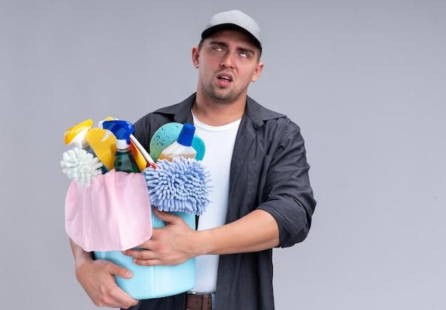 コピー スペースで白い壁に分離されたクリーニング ツールのバケツを保持している t シャツとキャップを着て疲れた若いハンサムな掃除男