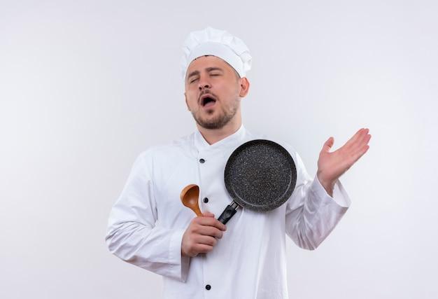 Stanco giovane cuoco bello in uniforme del cuoco unico che tiene cucchiaio e padella che mostra la mano vuota con gli occhi chiusi isolati su spazio bianco