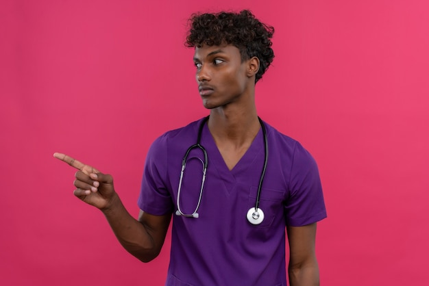 A tired young handsome dark-skinned doctor with curly hair wearing violet uniform with stethoscope pointing with index finger