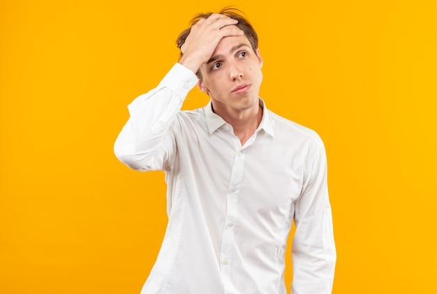 Stanco giovane bel ragazzo che indossa una camicia bianca che mette la mano sulla fronte isolata sul muro arancione
