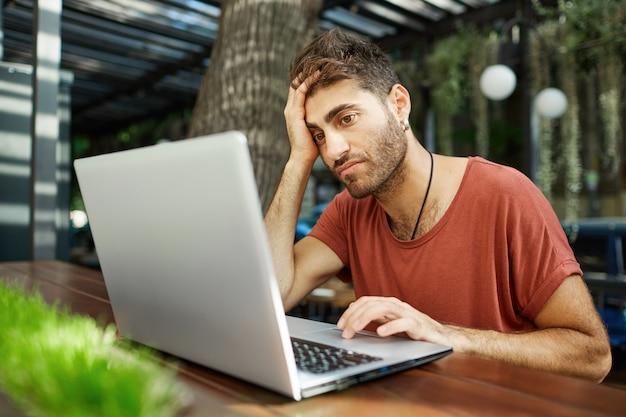 Усталый молодой красавец сидит с ноутбуком в летнем кафе, работает удаленно или учится с использованием паркового wi-fi