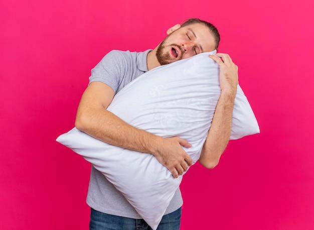 Усталый молодой красивый славянский больной обнимает подушку, кладя на нее голову с закрытыми глазами, изолированными на розовой стене
