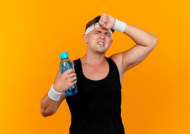 水のボトルを保持し、オレンジ色の背景で隔離の額に手を置くヘッドバンドとリストバンドを身に着けている疲れた若いハンサムなスポーティな男