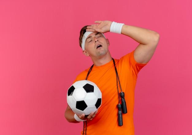 Усталый молодой красивый спортивный мужчина с головной повязкой и браслетами со скакалкой вокруг шеи, держащий футбольный мяч, положив руку на лоб с закрытыми глазами, изолированными на розовом фоне с копией пространства