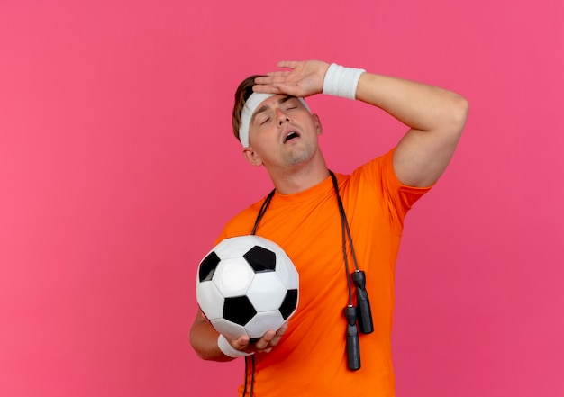Tired young handsome sporty man wearing headband and wristbands with jump rope around neck holding soccer ball putting hand on forehead with closed eyes isolated on pink background with copy space