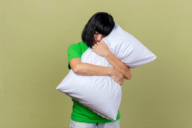 Усталая молодая больная кавказская девушка обнимает подушку с закрытыми глазами на оливково-зеленом фоне с копией пространства