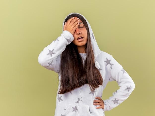目を閉じて疲れた若い病気の少女は、オリーブグリーンの背景に分離された額と腰に手を置くフードを着用します。