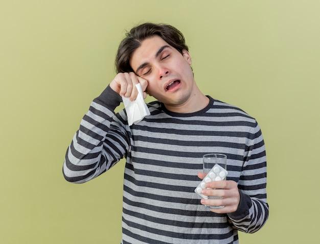 Stanco giovane uomo malato tenendo un bicchiere d'acqua con pillole e tovagliolo asciugandosi gli occhi con la mano isolato su verde oliva