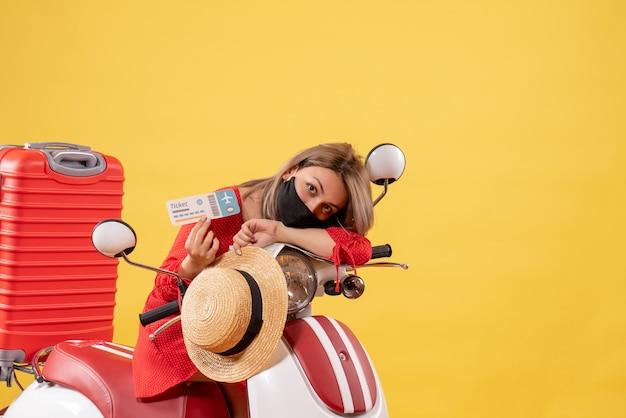 チケットを保持している赤いスーツケースを持った原付に疲れた若い女性