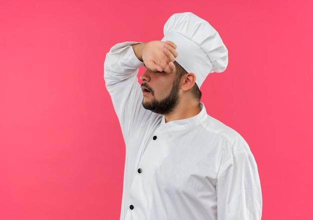 ピンクのスペースで隔離の額に手を置くシェフの制服を着た疲れた若い男性料理人