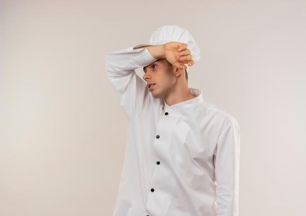 Cuoco maschio giovane stanco che indossa l'uniforme del cuoco unico che mette il polso sulla sua fronte con lo spazio della copia