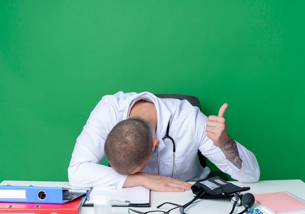 의료 가운과 청진기를 입고 피곤한 젊은 남성 의사가 책상과 머리에 손을 대고 손에 손을 잡고 엄지 손가락을 보여주는 작업 도구로 책상에 앉아 녹색 배경에 고립