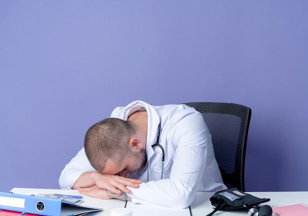 医療ローブと聴診器を身に着けている疲れた若い男性医師は、机の上に手を置き、紫色の背景で隔離の手に頭を置く作業ツールで机に座っています。