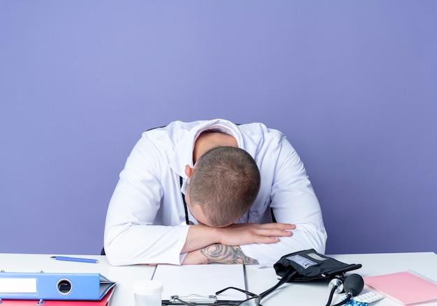 Stanco giovane maschio medico indossando abito medico e stetoscopio seduto alla scrivania con strumenti di lavoro mettendo le mani sulla scrivania e la testa sulle mani isolate su sfondo viola