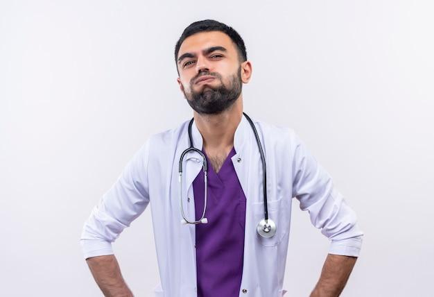 孤立した白い壁に聴診器の医療用ガウンを着て疲れた若い男性医師