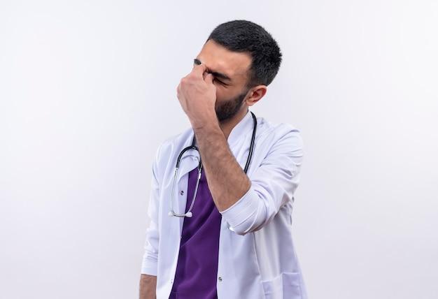 聴診器の医療用ガウンを身に着けている疲れた若い男性医師は、孤立した白に彼の手を置きます