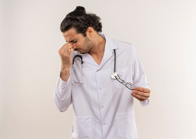 Giovane medico maschio stanco con vetri ottici che indossa una veste bianca con lo stetoscopio che mette la mano sulla fronte su bianco