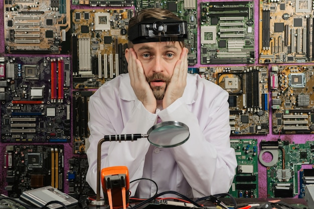 Усталый молодой инженер-электрик мужского пола, сидящий за столом в электролаборатории