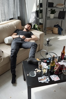 Tired young man in black jeans sleeping on sofa with leg on coffee table with beer and poker chips after hilarious party