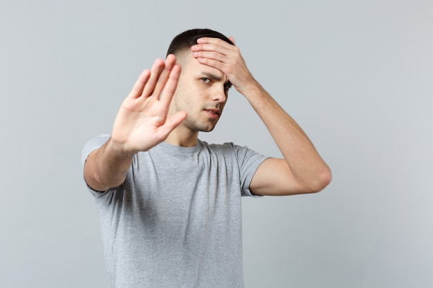 Tired young man in casual clothes putting hand on forehead, showing stop gesture with palm