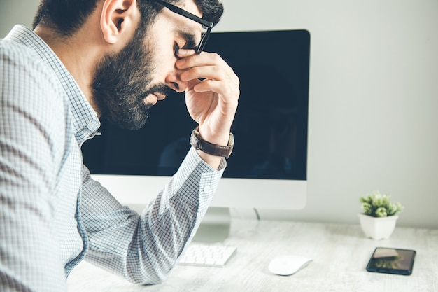 Усталый молодой человек чувствует боль, напряжение глаз держит очки, протирая сухие раздраженные глаза, устал от работы за компьютером