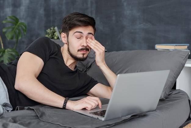 Усталый молодой человек с усталостью глаз, лежа на кровати с ноутбуком и протирая глаза