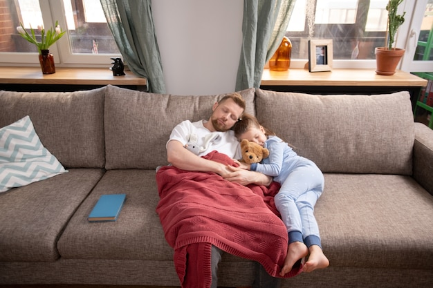 Tired young man and his cute little daughter in blue pajamas lying on soft couch by window in living-room and napping after dinner