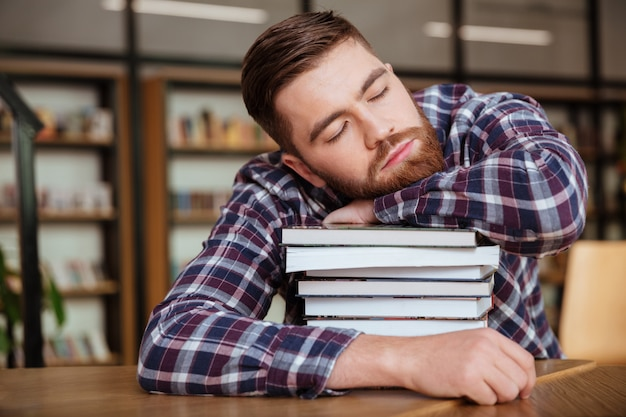 Tired young man holding his head on the book stack