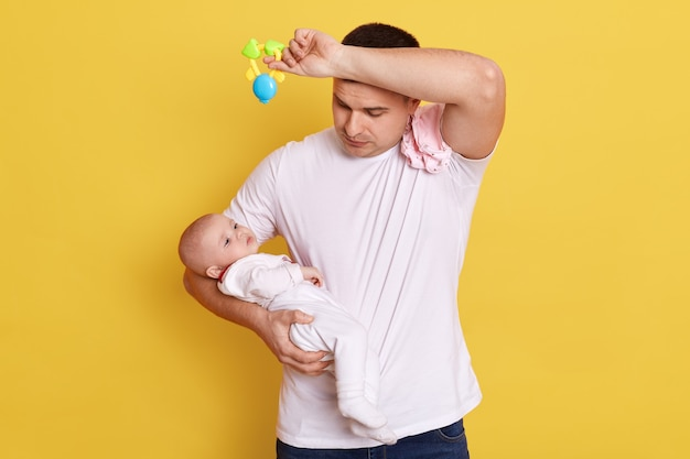 Усталый молодой человек в белой повседневной футболке держит в руках новорожденную дочь