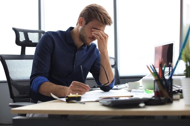 疲れた青年がオフィスに座って書類を扱っています。