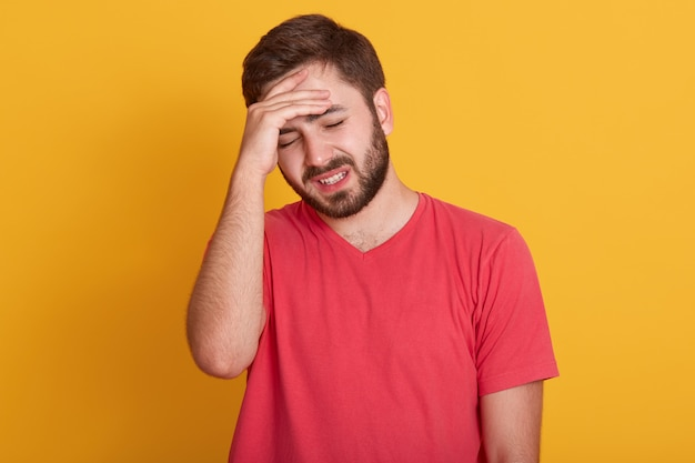 Tired young man keeps hand on forehead