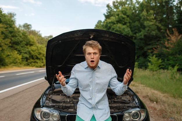 Tired young man at the opened hood, car breakdown. broken automobile or repairing of vehicle, trouble with auto engine on highway
