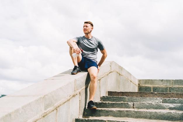 Усталый молодой человек-бегун сидит и расслабляется после спортивной тренировки, держа бутылку с водой во время занятий