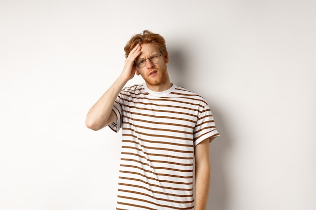 Tired young man student touching head, looking complex and tired, standing over white background.