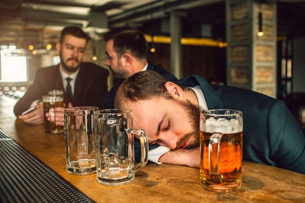 Tired young man in suit sleep on bar counter. he is drunk. there are two empty mugs and one full with beer. other two young men sit behind.