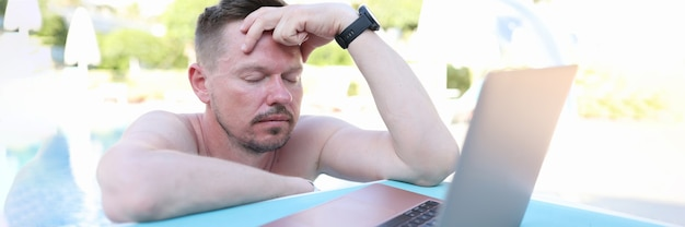 Tired young man with closed eyes in front of laptop stands in pool. time management at remote work concept
