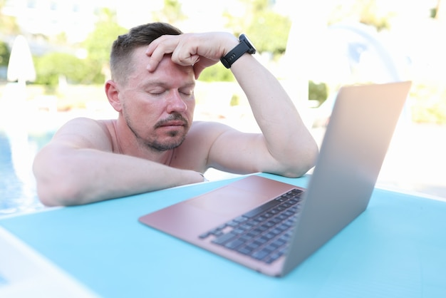 Tired young man with closed eyes in front of laptop stands in pool