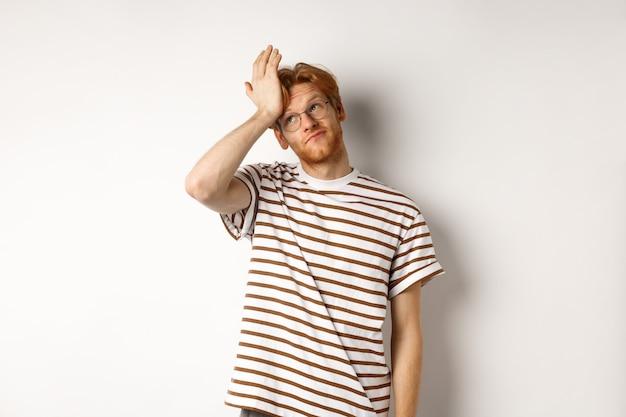 赤い髪と眼鏡、目を転がし、白い背景の上に立って、facepalmを悩ませている疲れた若い男。