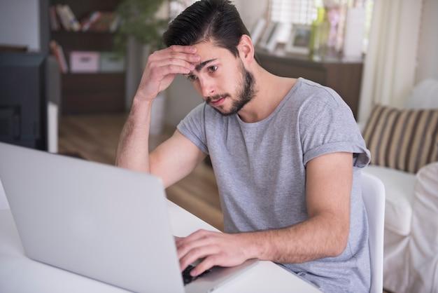 彼のラップトップで自宅で働く疲れた若い男