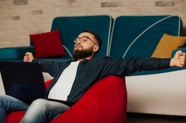 Усталый молодой менеджер работает из дома. устал после работы. технологии, удаленная работа и концепция образа жизни.