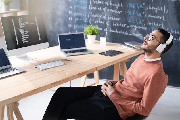 職場で休憩しながら椅子にリラックスしたポーズで座っているヘッドフォンで疲れた若い中東のコーダー