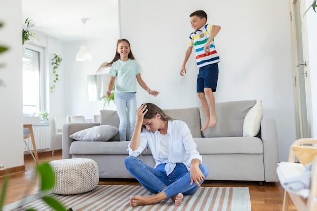 피곤한 젊은 어머니는 바닥에 앉아 노트북과 문서 작업을 하는 동안 어린 아이들이 소파에 뛰어오르며 즐겁게 놀고 소음을 냅니다.