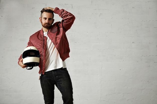 빨간색 폭격기 재킷, 검은 색 청바지 및 흰색 티셔츠에 피곤한 젊은 오토바이 운전자가 헤어 스타일을 조정하고 흰색 헬멧을 들고