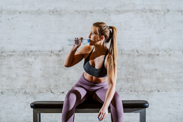 Tired young muscular fit attractive caucasian sportswoman in sportswear with ponytail sitting on the bench in gym and drinking water.