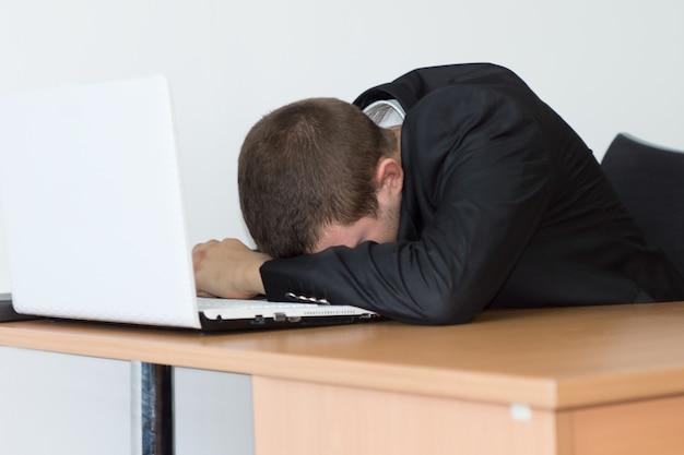검은 양복을 입은 피곤한 젊은 사무실 남자는 컴퓨터 앞에서 책상에서 낮잠을 자고 있습니다.